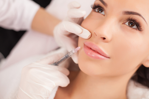 A cosmetic surgeon wearing white gloves injecting lip fillers into patient upper lip