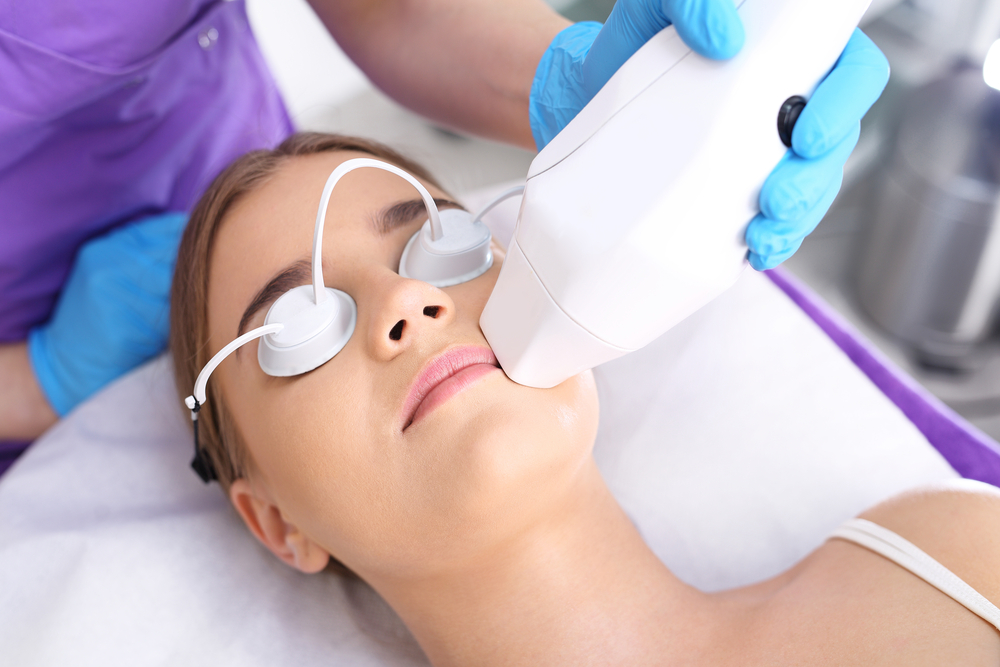 Nurse with blue gloves performing cosmetic laser treatment on a woman